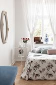 White Bedside Table With Fresh Red Roses, Candles And Coffee Cup In Real Photo Of Bright Bedroom Int poster