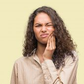 Young hispanic business woman touching mouth with hand with painful expression because of toothache  poster