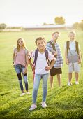 Portrait photo of a diverse group of smiling elementary school students standing in a school yard we poster