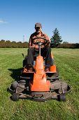 stock photo of grass-cutter  - Mature man driving grass cutter in a sunny day - JPG