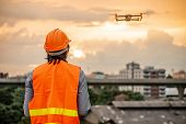 Young Asian Engineer Man Flying Drone Over Construction Site During Sunset. Using Unmanned Aerial Ve poster