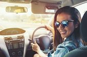 Happy Beauty Asian Woman Black Hair Smile With Sunglass And Blue Jean Jacket Driving Car At Sunset.  poster