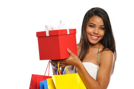 foto of african american woman  - Young African American woman holding a present and shopping bags isolated on white background - JPG
