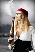 foto of pirate girl  - Girl pirate blows a smoke from a trunk of a old pistol - JPG