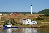 stock photo of acadian  - Picturesque rural scene with water and windmill on hillside - JPG