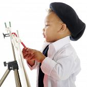 picture of french beret  - Closeup image of an adorable preschool artist painting on an easel in his smock and French beret - JPG