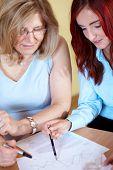 Постер, плакат: Старший и младший businesswoma работает на некоторые документы