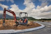 stock photo of earth-mover  - a digger in a new development area constructing road - JPG