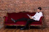 foto of settee  - Conceptual image of an elegant businessman lying relaxing on a settee against a brick wall and reading paperwork  - JPG