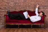 image of settee  - Conceptual image of an elegant businessman lying relaxing on a settee against a brick wall and reading paperwork - JPG