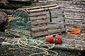 A wooden lobster trap with buoys and rope on a Newfoundland, Canada wharf.