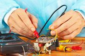 Master checks the electronic components of device with multimeter