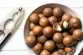 top view of macadamia nuts with nutcracker on white wooden table