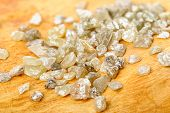 pic of uncut  - A pile of white grey uncut and rough diamonds on birch wood - JPG