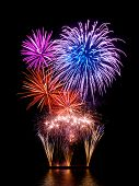 picture of firework display  - Magnificent fireworks display with happy colors on black background reflected on water - JPG