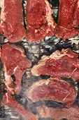 pic of brazier  - fresh raw beef meat fillet mignon on black grill grid over charcoal on brazier - JPG