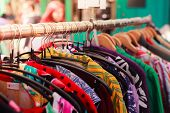 image of flea  - Clotes hanging on a rail at a street market outdoors - JPG