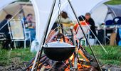 stock photo of food chain  - kettle on a tripod hanging around a bonfire - JPG