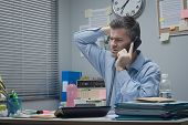 stock photo of confuse  - Confused employee on the phone at office desk touching his head - JPG