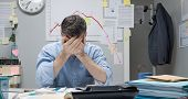 foto of nervous breakdown  - Desperate office worker with head in hands and negative financial chart on background - JPG