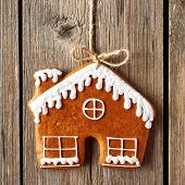 pic of gingerbread house  - Christmas homemade gingerbread house cookie over wooden background - JPG