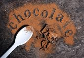 picture of slating  - Modern aerial view of chocolate on black slate bench top table with pale blue spoon spelling letters word with light chocolate dusting - JPG