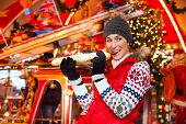 foto of merry-go-round  - Woman eating during advent season or holiday in front of a carousel or marry - JPG