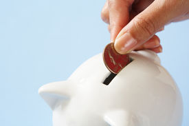 picture of save money  - A woman saving a coin into a piggy bank - JPG
