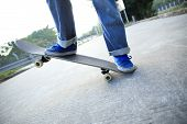 stock photo of skateboarding  - closup of young skateboarder skateboarding legs at skatepark - JPG