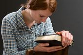 stock photo of god  - A woman sits on an old wooden chair with a Bible in her hands and prays to God - JPG