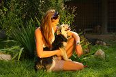 picture of stray dog  - A young beautiful woman with blonde hair is holding lovingly a stray dog in her arms in a backyard - JPG