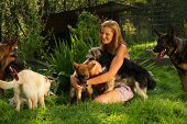 pic of tickle  - A young beautiful woman with blonde hair is playing lovingly with a bunch of dogs in a backyard garden with green grass - JPG