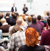 stock photo of speaker  - Speaker at Business Conference and Presentation. Audience in the conference hall. Business and Entrepreneurship. Copy space on white screen.