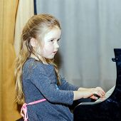 pic of grand piano  - Cute little girl playing grand piano in concert hall