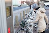 picture of fleet  - Lady dialing on keyboard of urban bicycle station - JPG