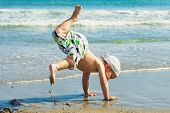 stock photo of break-dance  - Little boy dancing break dance on the beach - JPG