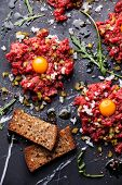 picture of tartar  - Beef tartare with fresh toasts on dark marble background - JPG