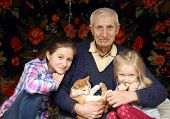 stock photo of granddaughters  - portrait of sitting senior man and granddaughters at home - JPG