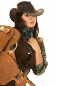 stock photo of cowgirls  - A cowgirl with a serious expression holding on to her saddle.