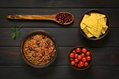 stock photo of kidney beans  - Overhead shot of chili con carne and tortilla chips with ingredients dried kidney beans and cherry tomatoes photographed on dark wood with natural light - JPG