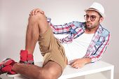 stock photo of knee-cap  - Young fashion man lying on a white table holding one knee up - JPG