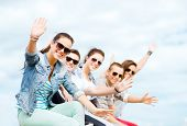 stock photo of waving hands  - summer holidays and teenage concept  - JPG