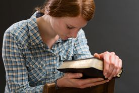pic of hand god  - A woman sits on an old wooden chair with a Bible in her hands and prays to God - JPG
