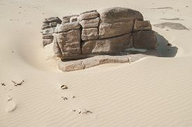 picture of gneiss  - Outcrop of jointed gneiss surrounded by soft pale beach sand with windblown ripples - JPG