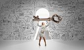 stock photo of keyhole  - Young businesswoman and keyhole at background lifting big key above head - JPG