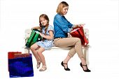 stock photo of wonderful  - Happy mother and daughter with shopping bags sitting at studio - JPG