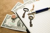 stock photo of memento  - Opened notebook with a blank sheet pen keys and money on the old tissue - JPG