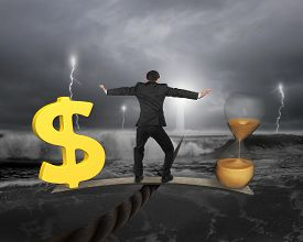 picture of time-saving  - Man standing on wood board between hourglass and golden dollar sign balancing on wire with dark stormy ocean background - JPG