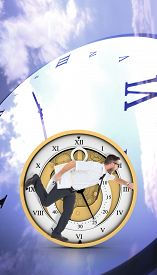 picture of running-late  - Geeky young businessman running late against digitally generated roman numeral clock - JPG
