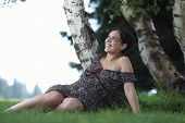 Pretty young woman posing/sitting on a lawn, outdoors in a park and smiling